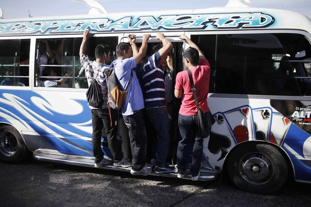People ride a mini bus during a suspension of public transport services in San Salvador July 27, 2015. A suspension of public bus services was called following threats to drivers and passengers by gang members, according to local media. (Photo by Jose Cabezas/Reuters)