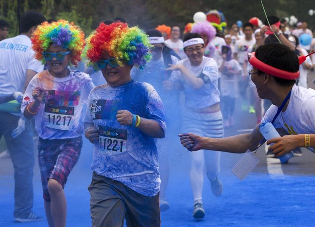 "Participants are sprayed by color powder as they run through a ""color station"" during the five-kilometer color run event held in Beijing, China Saturday, June 21, 2014. (Photo by Andy Wong/AP Photo)"