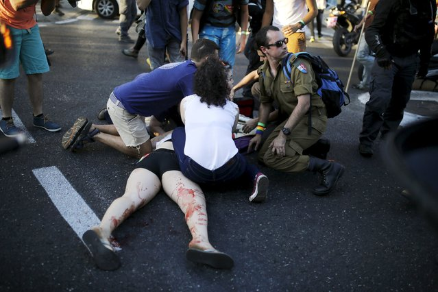 Participants of a gay pride parade in Jerusalem treat an injured person after an Orthodox Jewish assailant stabbed and injured six participants in the annual march in Jerusalem on Thursday, police and witnesses said July 30, 2015. (Photo by Amir Cohen/Reuters)