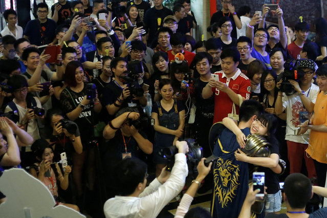 """Haokun Xue, a 26-year-old fan from Shandong Province, and his fiancé Na Li hug after his proposal was accepted during China's premiere of the film """"Warcraft"""" at a theatre in Shanghai, China June 7, 2016. (Photo by Aly Song/Reuters)"""