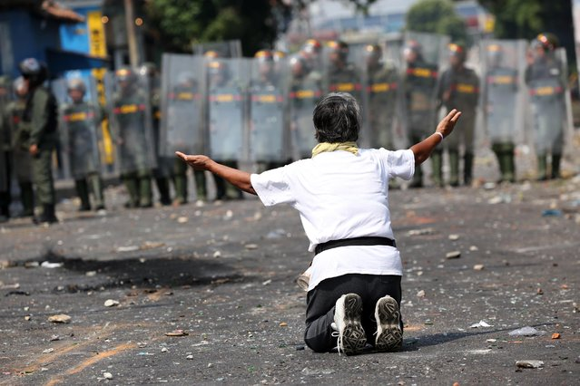 A demonstrator kneels down in front of security forces in Urena, Venezuela, February 23, 2019. (Photo by Andres Martinez Casares/Reuters)