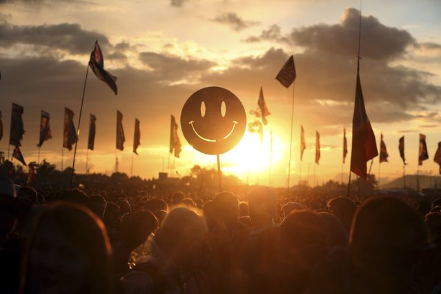 A festival-goer holds up a smiley face as the sun sets in front of the Other Stage at Worthy Farm in Somerset, during the Glastonbury Festival June 27, 2014. (Photo by Cathal McNaughton/Reuters)