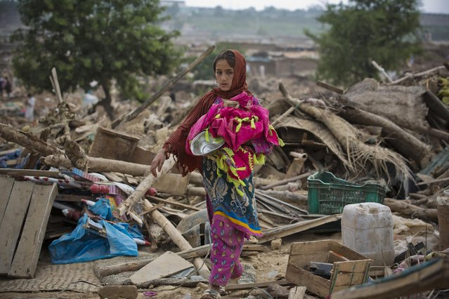 A girl collects her belongings from the debris of her house bulldozed by the government, in slums of Islamabad, Pakistan, Friday, July 31, 2015. (Photo by B. K. Bangash/AP Photo)