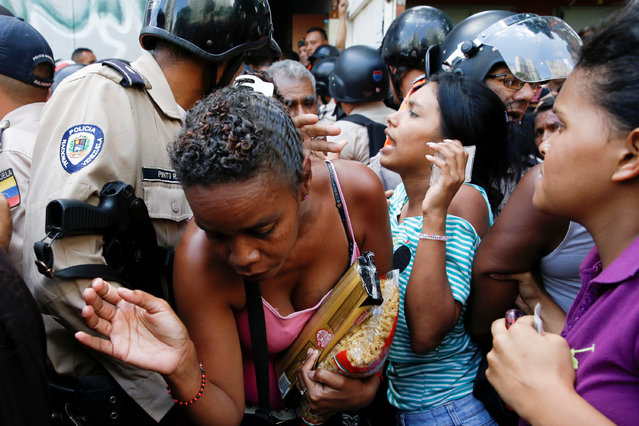 A woman carrying packages of pasta tries to walks out from a gathering while riot police try to control the crowd outside a supermarket in Caracas, Venezuela, June 10, 2016. (Photo by Carlos Garcia Rawlins/Reuters)