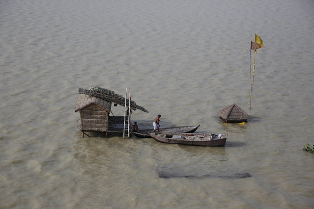 In this July 30, 2015 file photo, a Hindu holy man gets into a boat after the hut where he lives was surrounded by flood waters of the River Ganges in Allahabad, India. The Ganges, one of India's largest rivers is flooded following monsoon rains. (Photo by Rajesh Kumar Singh/AP Photo)