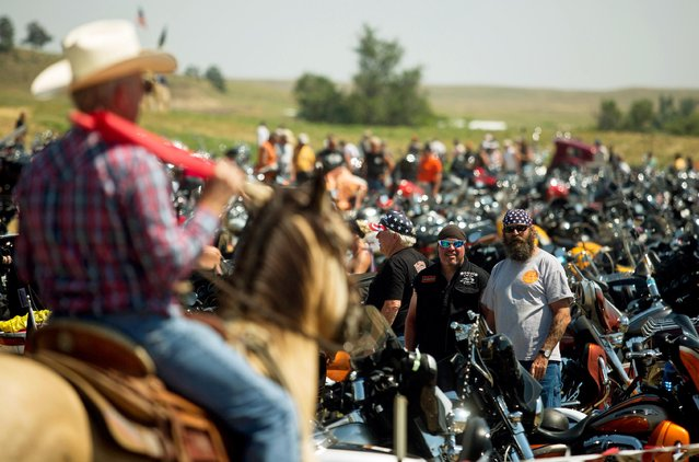 Kirk Cordes (L), on his horse Lash, direct traffic at the Stone House Saloon outside of Belle Fourche, South Dakota, while participating in the annual Sturgis Motorcycle Rally in South Dakota, August 5, 2015. (Photo by Kristina Barker/Reuters)