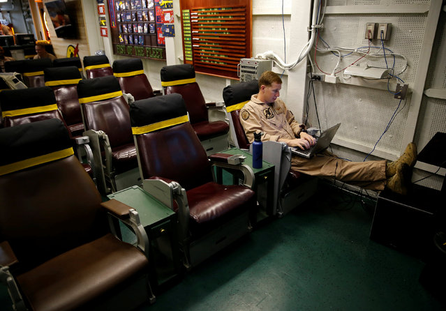 A pilot sits in the squadron room on board the USS Harry S. Truman aircraft carrier in the eastern Mediterranean Sea, June 14, 2016. (Photo by Baz Ratner/Reuters)