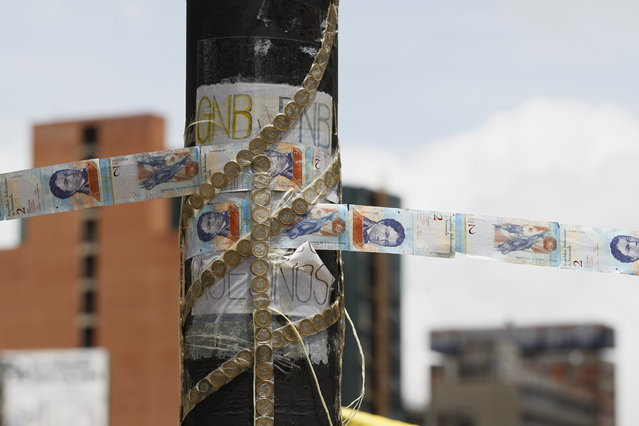 In this Thursday, July 20, 2017 photo, devalued Bolivar bank notes and coins, taped together, serve as makeshift rope at a roadblock set up by anti-government protesters in Caracas, Venezuela. Large swaths of Venezuela's capital was silent Thursday as opponents of President Nicolas Maduro called a major national strike as an expression of disapproval of his plan to convene a constitutional assembly that would reshape the Venezuelan system to consolidate the ruling party's power over the few institutions that remain outside its control. (Photo by Ariana Cubillos/AP Photo)