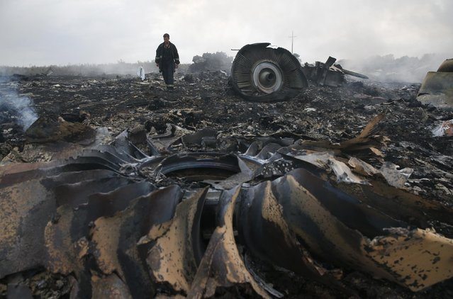 An Emergencies Ministry member walks at a site of a Malaysia Airlines Boeing 777 plane crash near the settlement of Grabovo in the Donetsk region, July 17, 2014. The Malaysian airliner flight MH-17 was brought down over eastern Ukraine on Thursday, killing all 295 people aboard and sharply raising the stakes in a conflict between Kiev and pro-Moscow rebels in which Russia and the West back opposing sides. (Photo by Maxim Zmeyev/Reuters)