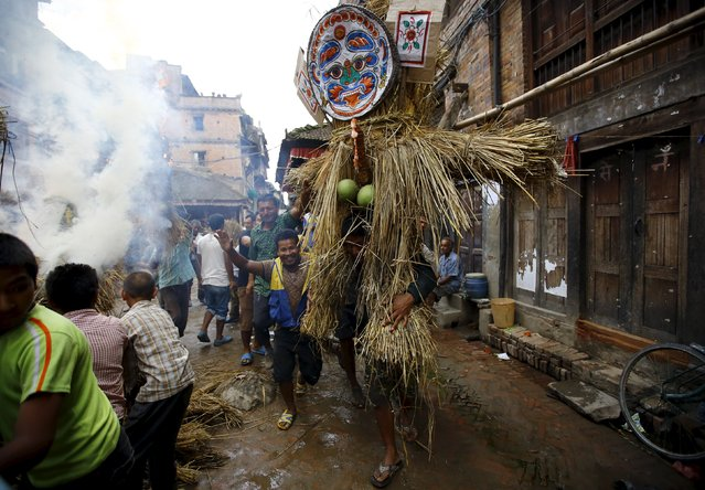 People carry an effigy of the demon Ghantakarna, while another effigy of the demon is burnt to symbolize the destruction of evil, during the Ghantakarna festival in the ancient city of Bhaktapur, Nepal August 12, 2015. (Photo by Navesh Chitrakar/Reuters)