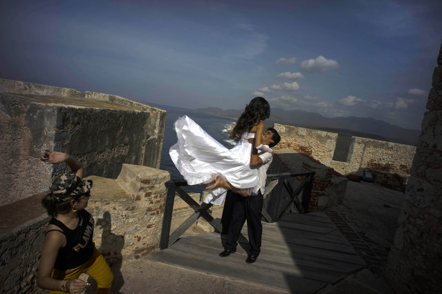 In this July 27, 2015 photo, newlyweds pose for photos during their photo session at the fortress of the Morro in Santiago, Cuba. While Cuban cities are seeing stagnant visitor numbers, cruise ships provide a promising new potential source of visitors, although dockings remain relatively rare. (Photo by Ramon Espinosa/AP Photo)