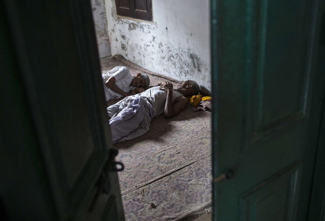 Hindu priests rest in their room after conducting morning prayers at Mukti Bhavan (Salvation House) in Varanasi, in the northern Indian state of Uttar Pradesh, June 17, 2014. (Photo by Danish Siddiqui/Reuters)