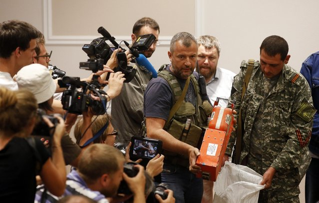 A pro-Russian separatist shows members of the media a black box belonging to Malaysia Airlines flight MH17, before its handover to Malaysian representatives, in Donetsk July 22, 2014. The remains of some of the 298 victims of the Malaysia Airlines plane downed over Ukraine were making their way to the Netherlands on Tuesday as Aleksander Borodai handed over the plane's black boxes to Malaysian experts. (Photo by Maxim Zmeyev/Reuters)
