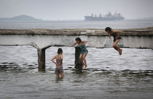 Girls jump off a pier along the beach, Tuesday, June 21, 2016, in Wongson, North Korea. Wonsan, about 125 miles from Pyongyang, is a port city located in Kangwon Province, North Korea along the eastern side of the Korean Peninsula and was one of the cities chosen to be developed into a summer destination for locals as well as tourists. (Photo by Wong Maye-E/AP Photo)