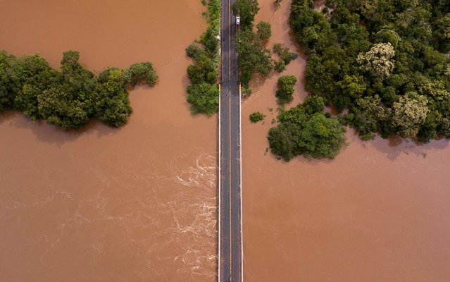 View of a bridge almost consumed by flood water on the border of the municipalities of Diamantina and Olhos D'Agua in Minas Gerais state, Brazil, on January 28, 2020. The levels of the Jequitinhonha River have risen to alarming levels following severe flooding in the state, which has already claimed close to 50 confirmed deaths and almost 19,000 people have been forced from their homes due to flood or landslide damage. (Photo by Nilmar Lage/AFP Photo)