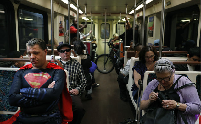 "In this Tuesday, May 16, 2017 photo, superhero impersonator Justin Harrison, left, rides a Metro train wearing a Superman costume on his way to Hollywood Boulevard in Los Angeles. ""I always go out in a costume"", said Harrison. ""I love seeing people happy and seeing them smile"". (Photo by Jae C. Hong/AP Photo)"
