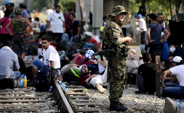 Macedonian special police guard the border as more than a thousand immigrants wait at the border line of Macedonia and Greece to enter Macedonia near the Gevgelija railway station August 20, 2015. (Photo by Ognen Teofilovski/Reuters)