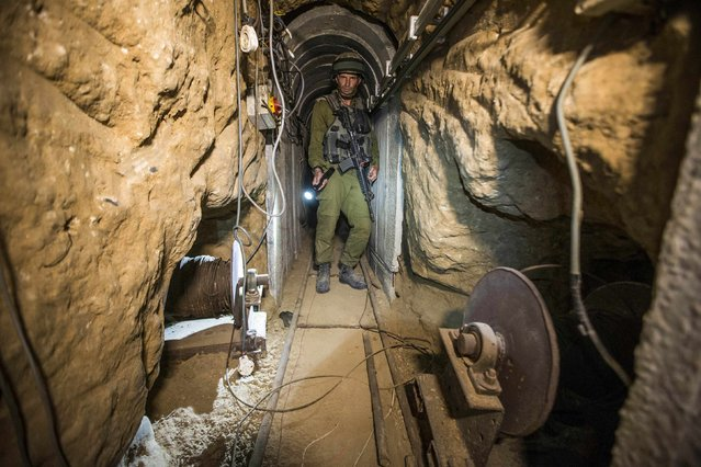 An Israeli army officer gives explanations to journalists during an army organised tour in a tunnel said to be used by Palestinian militants for cross-border attacks, July 25, 2014. (Photo by Jack Guez/Reuters)