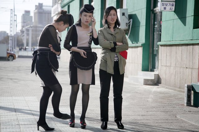In this Wednesday, April 12, 2017, photo, waitresses wait outside a restaurant in Pyongyang, North Korea. A generational divide is quietly growing in North Korea, often hidden behind relentless propaganda. On the streets there are young women in not-quite mini-skirts and teenage boys with baseball hats cocked sideways, K-pop style. (Photo by Wong Maye-E/AP Photo)