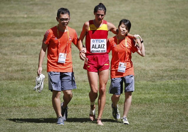 Roberto Alaiz of Spain (C) is helped by staff after retiring injured from the 3,000 metres steeplechase heat 3 during the 15th IAAF World Championships at the National Stadium in Beijing, China August 22, 2015. (Photo by David Gray/Reuters)