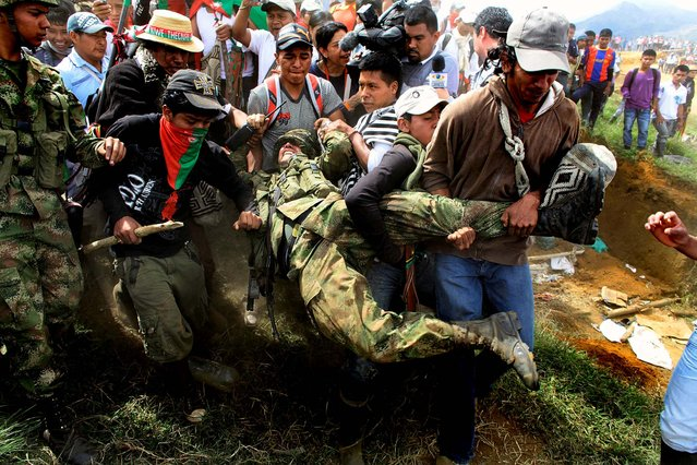 Nasa Indians drag off a soldier in Toribio, southern Colombia on July 17, 2012. Leaders of the 115,000 Nasa people are demanding government troops and leftist rebels alike go away and leave them in peace. (Photo by William Fernando Martinez/Associated Press)