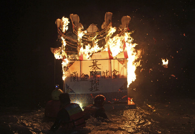 In this photo made early Sunday, August 10, 2014, in Keelung, Taiwan, worshippers guide a burning model house draped with a message for a deceased family member out to the ocean as an offering to appease wandering ghosts during the Chinese folklore's mid-summer's Ghost Month Festival. (Photo by Chiang Ying-ying/AP Photo)