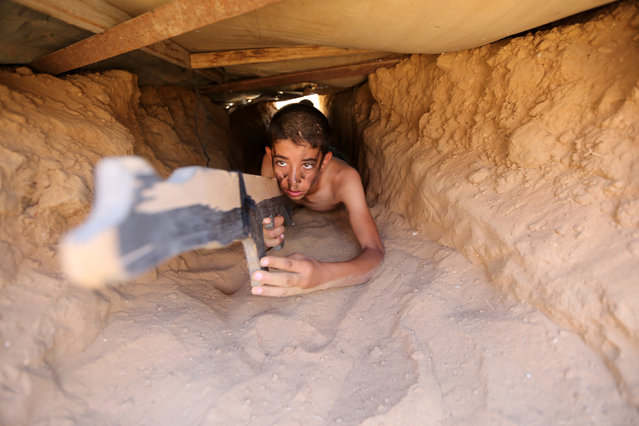 A young Palestinian crawls through a tunnel during a military-style exercise at a summer camp organised by the Islamic Jihad Movement in Khan Younis in the southern Gaza Strip July 13, 2016. (Photo by Ibraheem Abu Mustafa/Reuters)