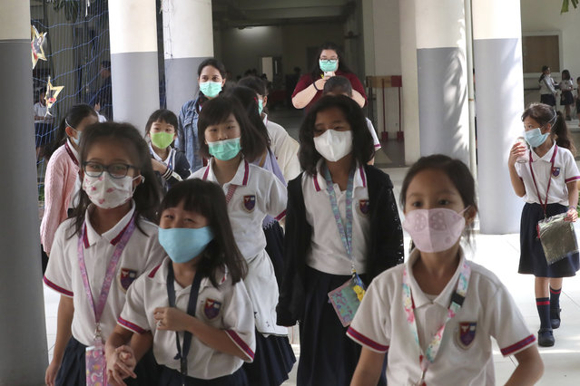 Students wear masks at Jakarta Nanyang School in Serpong on the outskirts of Jakarta, Indonesia, Tuesday, March 3, 2020. Indonesia confirmed its first cases of the coronavirus Monday in two people who contracted the illness from a foreign traveler. (Photo by Tatan Syuflana/AP Photo)