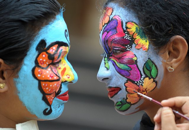 """Indian nursing students participate in a face painting competition on the theme of """"preserving the nature"""" at Vijay Marie College of Nursing in Hyderabad on August 11, 2014 on the occasion of  the country's upcoming Independence Day celebrations. India celebrates its anniversary of Independence from Britian on August 15. (Photo by Noah Seelam/AFP Photo)"""