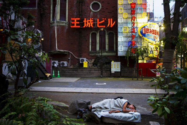 A man sleeps in a courtyard of the nightlife district in Shinjuku in Tokyo, August 27, 2015. (Photo by Thomas Peter/Reuters)