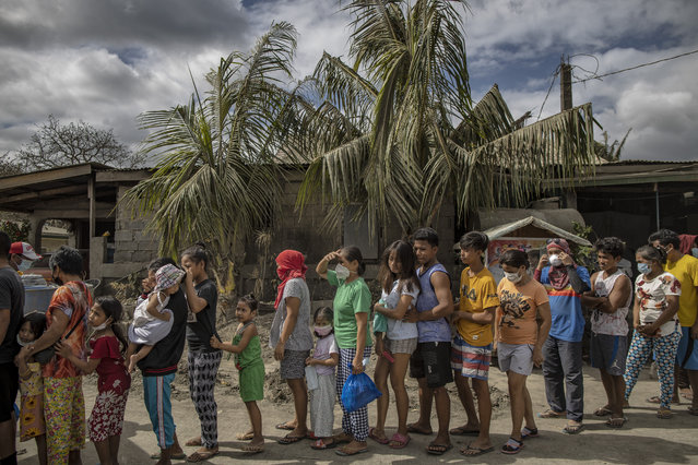 Residents queue up to receive relief goods on January 19, 2020 in the village of San Guillermo, Talisay, Batangas province, Philippines. The Philippine Institute of of Volcanology and Seismology has maintained the alert level four out of five, warning that a hazardous eruption could take place anytime, as authorities have evacuated at least 50,000 people from areas surrounding the volcano. An estimated $60 million worth of crops and livestock have been damaged by the on-going eruption, according to the country's agriculture department. (Photo by Ezra Acayan/Getty Images)