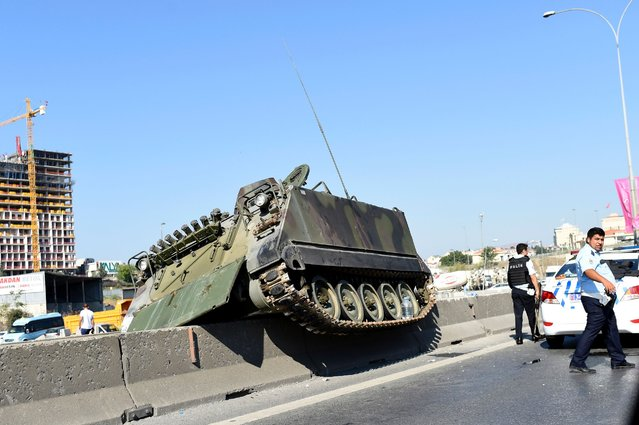 This picture taken on July 16, 2016 shows a tank stucks on a median strip as Turkish police officers walk around it after they took over a military position at the Anatolian side at Uskudar in Istanbul on July 16, 2016. (Photo by Bulent Kilic/AFP Photo)