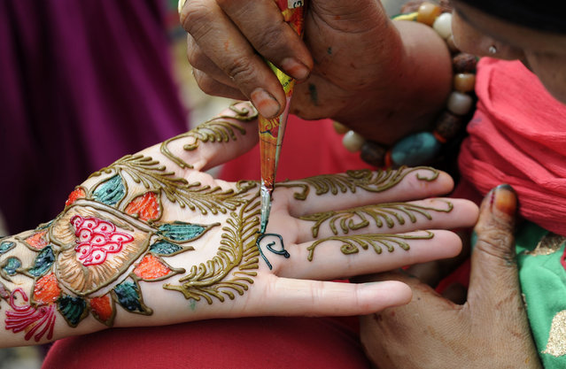 An artist decorates the hand of a Nepalese devotee with mehendi (henna) during Shravan festivities in Kathmandu on July 18, 2016. According to the Nepali calendar, Shravan is considered the holiest month of the year with each Monday of the month known as Shravan Somvar, when worshippers offer prayers for a happy and prosperous life. (Photo by Prakash Mathema/AFP Photo)