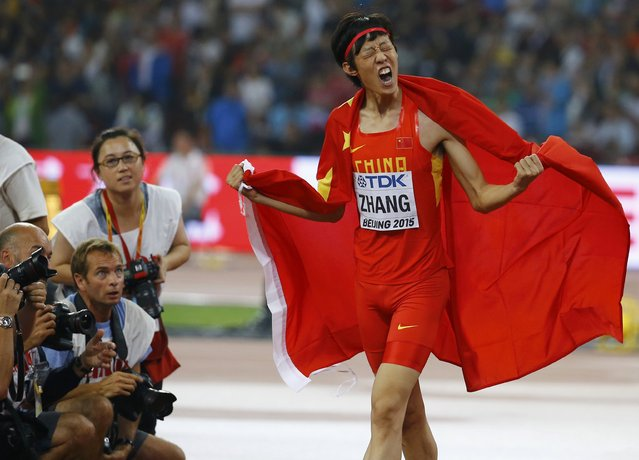 Second placed Zhang Guowei of China celebrates with a national flag after winning silver in the men's high jump final during the 15th IAAF World Championships at the National Stadium in Beijing, China, August 30, 2015. (Photo by David Gray/Reuters)