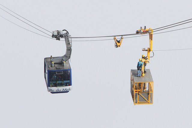 Rescuers ride on a rescue basket as they work to evacuate people stuck in a cable car leading to the Pic du Midi de Bigorre, southern France, on August 20, 2014, following an electric failure. 55 people were stuck all afternoon on August 20 in two cable cars at the Pic du Midi de Bigorre, one ascending and the other descending. (Photo by Laurent Dard/AFP Photo)