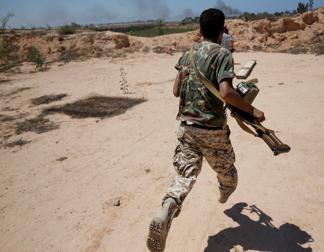 A fighter of Libyan forces allied with the U.N.-backed government runs for cover during a battle with Islamic States fighters in Sirte, Libya, July 21, 2016. (Photo by Goran Tomasevic/Reuters)