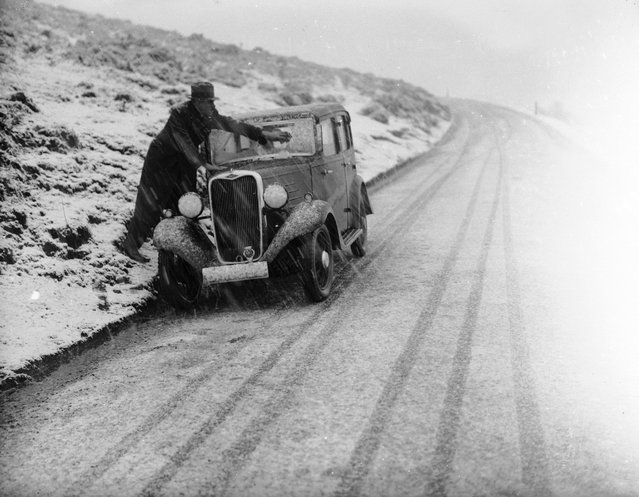 A driver on the Horseshoe Pass in North Wales wiping the snow from the windscreen of his car during a heavy snow storm, 18th January 1937. (Photo by Norman Smith)