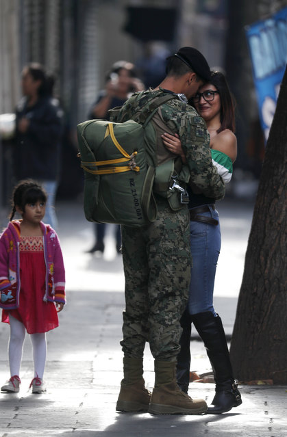 In this September 16, 2017. photo, a soldier embraces a woman before the start of the annual Independence Day military parade in Mexico City's main square, known as the Zocalo. Mexico is marking the 207th anniversary of its independence from Spain. (Photo by Eduardo Verdugo/AP Photo)