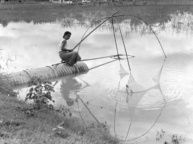 A woman fishing in a residential section of Vientiane, the capital and largest city of Laos, 1961. (Photo by Keystone Features)