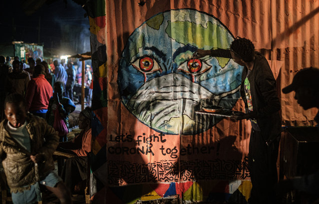 Kenyan visual artist Grandsan paints graffiti, that shows the earth wearing a mask, to increase awareness of the prevention against the COVID-19 coronavirus at a butcher shop in Kibera, Kenya, on March 23, 2020. (Photo by Yasuyoshi Chiba/AFP Photo)