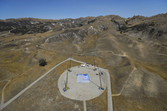 In this Monday, July 25, 2016 photo, cranes stand on the ground as production crew members set up a net about one-third the size of a football field and 20 stories high ahead of skydiver Luke Aikins' landing attempt without a parachute or wing suit in Simi Valley, Calif. (Photo by Jae C. Hong/AP Photo)
