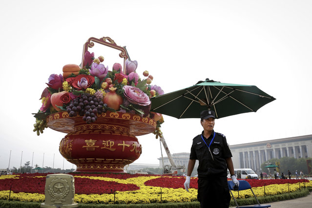 A security officer stands watch near a giant basket decorated with replicas of flowers and fruits on display at Tiananmen Square in Beijing, Monday, September 25, 2017. Hundreds of thousands foreign and domestic tourists are expected to flock to the square to celebrate the National Day and Mid-Autumn Festival over the week-long holidays starting on Sept. 30. (Photo by Andy Wong/AP Photo)