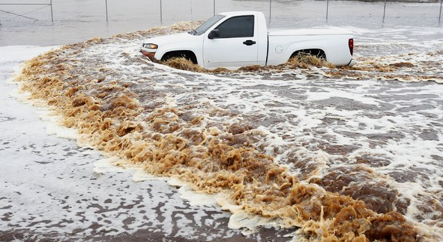 A truck creates a wake as its driver tries to navigate a severely flooded street as heavy rains pour down Monday, September 8, 2014, in Phoenix. Storms that flooded several Phoenix-area freeways and numerous local streets during the Monday morning commute set an all-time record for rainfall in Phoenix in a single day. (Photo by Ross D. Franklin/AP Photo)
