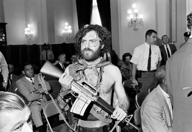 Jerry Rubin, prominent in the Yippie movement, arrives at House Un-American Activities Committee hearing in Washington on October 3, 1968, in his customary garb and carrying his toy plastic machine gun. Rubin was scheduled to be the first witness of the day's session inquiring into the disorders in Chicago during the Democratic National Convention. (Photo by Charles Harrity/AP Photo)