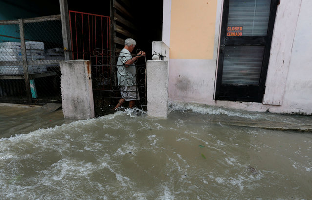 A man walks through flooded streets, after Hurricane Earl hit, in Belize City, Belize August 4, 2016. (Photo by Henry Romero/Reuters)