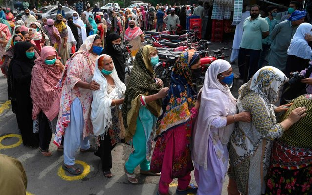 Residents wearing facemasks line up in a queue outside the National Database and Registration Authority (NADRA) office for new registrations and biometric verification under the governmental Ehsaas Emergency Cash Programme for families in need during a government-imposed nationwide lockdown as a preventive measure against the COVID-19 coronavirus, in Lahore on May 4, 2020. (Photo by Arif Ali/AFP Photo)