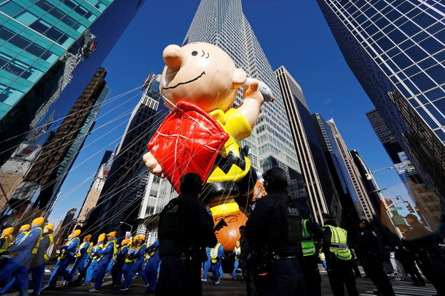 New York Police Department officers stand on guard as the Charlie Brown balloon make its way down 6th Ave during the 91st Macy's Thanksgiving Day Parade in the Manhattan borough of New York City, The  York, U.S., November 23, 2017. (Photo by Shannon Stapleton/Reuters)