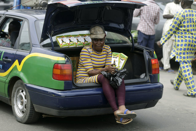 A woman sells herbal medicine from the back of a car, outside the Central Mosque in Lagos, Nigeria, Friday, March 20, 2020. The government banned all religious activities for four weeks following confirmation of coronavirus cases in the country. (Photo by Sunday Alamba/AP Photo)