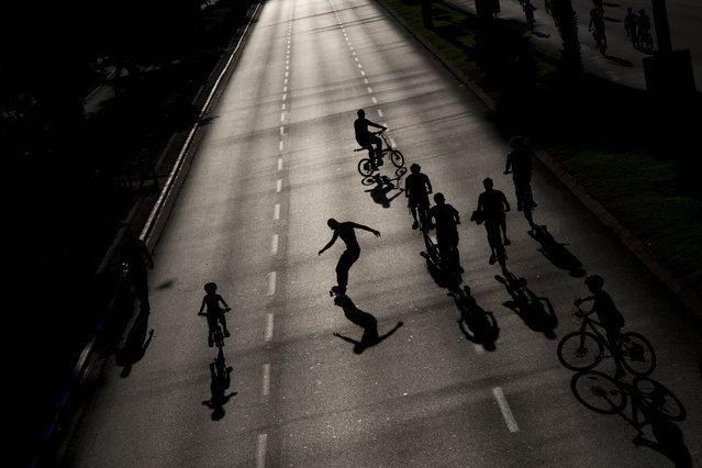 """Israelis ride their bicycles and skateboards on a car-free highway, during the holiday of Yom Kippur in Tel Aviv, Saturday, October 4. 2014. Israelis are marking Yom Kippur, or """"Day of Atonement"""", which is the holiest of Jewish holidays when observant Jews atone for the sins of the past year and the Israeli nation comes to almost a complete standstill. Yom Kippur coincides with the Muslim holiday of Eid al-Adha, the first time this has happened since 1981. (Photo by Oded Balilty/AP Photo)"""