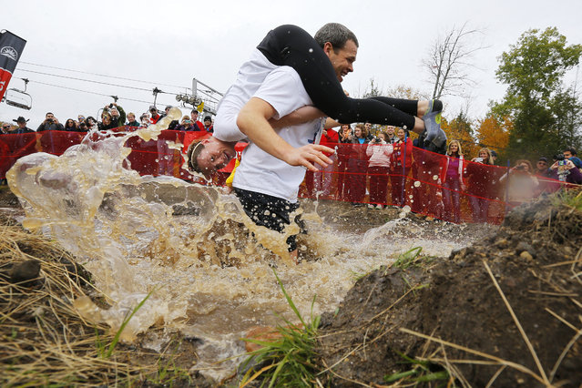 Seth Swanberg carries Lisa Swanberg through the water pit while competing in the North American Wife Carrying Championship at Sunday River ski resort in Newry, Maine October 11, 2014. REUTERS/Brian Snyder